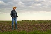 foto of farm land  - Portrait of Adult Female Farmer Standing on Fertile Agricultural Farm Land SoilLooking into Distance - JPG