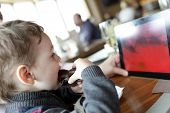 stock photo of eclairs  - Child has eclair and looking at tablet PC in the cafe - JPG