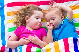 image of little sister  - Two kids sleeping in bed under colorful blanket - JPG