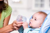 stock photo of drinking water  - Baby drinking water from bottle sitting in the highchair in kitchen - JPG