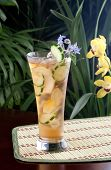 stock photo of borage  - Closeup of glass of ginger and cucumber iced tea garnished with borage flowers on a table in a restaurant on a tropical beach. ** Note: Slight graininess, best at smaller sizes - JPG