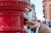 Throwing A Letter In A Red British Post Box poster