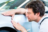 Male mechanic examine car finish on dents or scratches in workshop  poster