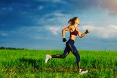 Young slim sports woman running on summer field poster