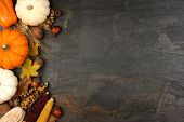 Autumn Harvest Side Border With Pumpkins, Leaves And Nuts Over A Slate Stone Background poster
