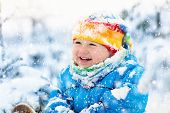 Baby Playing With Snow In Winter. Child In Snowy Park. poster