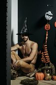 Halloween Macho In Witch Hat And Bared Torso Sitting poster