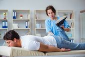 Female chiropractor doctor massaging male patient poster