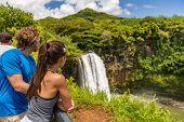 Couple tourists at Hawaii Kauai waterfall. Tourist visiting the Wailua Falls of Kauai Hawaii, hiking poster