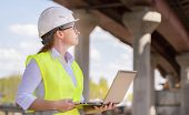 Female Foreman Working On Laptop At Bridge Construction Site. Girl Builder Controls Erection Of Car  poster