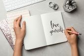 Woman Writing Love Yourself In Journal On Grey Table, Flat Lay poster