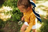 Overhead View Image Of Little Girl Exploring The Nature With Magnifying Glass Outdoors. Child Playin poster