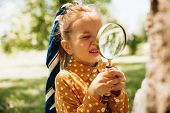 Portrait Of Cute Little Girl Learning And Exploring The Nature With Magnifying Glass Outdoors. Child poster