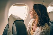 Traveler Girl Watching Through Airplane Window. Young Traveler Girl In Vacation. Girl Traveling By A poster
