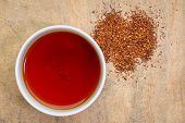 rooibos red tea  -  a white cup of a hot drink and loose leaves, tea made from the South African red poster