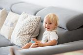 Adorable Baby Boy Drinking Milk From A Bottle In A White Sunny Living Room. poster