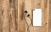 The White Back Side Of A Mobile Phone With Headphones Lies On An Old Wooden Background. Grunge Woode poster
