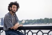 Dreamy And Romantic Homeless Man Sits On The Parapet Of Waterfront poster