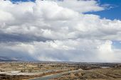 pic of semi-arid  - storm front over a mountain range at the edge of a flat semi - JPG