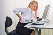 a woman with back pain from sitting so long in the office. health and welfare at work.