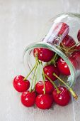stock photo of picking tray  - Freshly picked ripe cherries with stem and leaves in front of a preserving jar filled with cherries - JPG