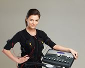 stock photo of stimulation  - Young woman in training costume near Electro Muscular Stimulation EMS machine  - JPG