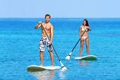stock photo of paddling  - Paddleboard beach people on stand up paddle board surfboard surfing in ocean sea on Big Island - JPG