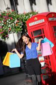 London shopper girl happy excited holding shopping bags by red phone booth. Woman shopping smiling i