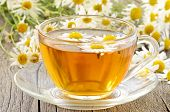 stock photo of chamomile  - Herbal chamomile tea with chamomile flowers on wooden table