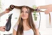 foto of brown-haired  - Hairdressers straightening long brown hair with hair dryer and round brush and hair irons - JPG