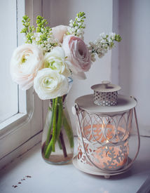 stock photo of buttercup  - Home festive decorations elegant bouquet of flowers buttercups and white lilac and candle lantern on white vintage windowsill - JPG