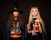 image of antichrist  - Halloween girls with lanterns looking at camera in the dark - JPG