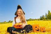 stock photo of pirate girl  - Halloween girl in costume of a pirate sitting on yellow grass with pumpkin and pail near her - JPG
