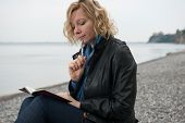 image of poetry  - Woman writing her thoughts or poetry by the sea - JPG
