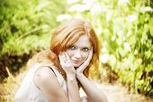stock photo of freckle face  - Portrait of redhead girl with blue eyes on nature - JPG
