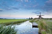 stock photo of windmills  - Dutch windmill by river at sunset Holland - JPG