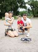 picture of scared baby  - Young family with two boys playing with RC quadrocopter toy - JPG