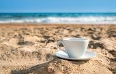 stock photo of beach shell art  - white cup with tea or coffee on sand beach front of sea close up  - JPG