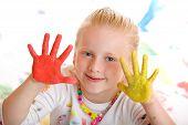 Постер, плакат: Молодой счастливый улыбающийся ребенок рисует с красочными палец краска