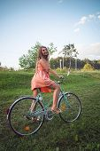 pic of riding-crop  - Pretty blonde riding her bicycle on field wearing a sexy cropped coral dress - JPG