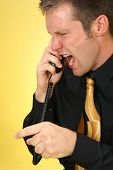 stock photo of angry man  - Angry 26 year old man yelling into phone - JPG