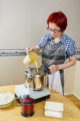 pic of food processor  - Woman adding mixture of milk and melted butter into food processor when baking - JPG
