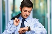 image of late 20s  - Young businessman checking time on his watch - JPG
