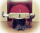 image of sawing  - Magician sawing a woman with a saw - JPG