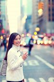 stock photo of cabs  - Professional young urban casual business woman in New York City Manhattan drinking coffee walking in street wearing coat downtown with yellow taxi cabs in background - JPG