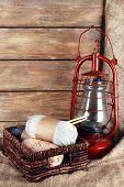 stock photo of kerosene lamp  - Kerosene lamp with yarn and needles for knitting in wicker basket on wooden planks background - JPG