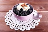image of doilies  - Dessert with prunes and almonds in bowl on lace doily and wooden planks background - JPG
