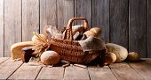 stock photo of wooden basket  - Different bread in wicker basket on table on wooden background - JPG
