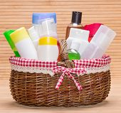 picture of cosmetic products  - Wicker basket filled with different cosmetic products for body care - JPG
