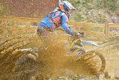 picture of motocross  - Motocross racer on wet and muddy terrain - JPG